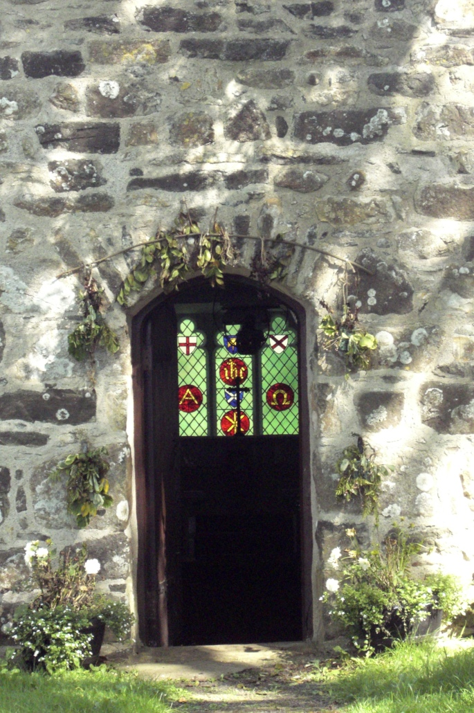 St Tudwens church, stained glass window through door